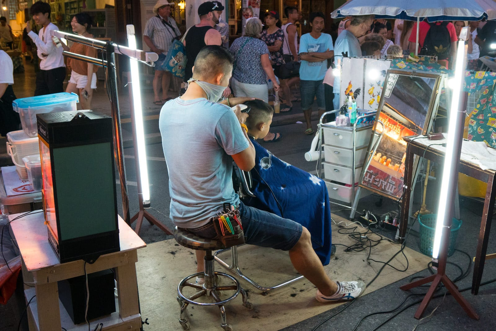 A hairdresser at his work on the Walking Street